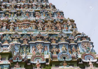 KUMBAKONAM, INDIA - OCTOBER 12, 2013: Mahalingeswarar Temple. Statue composition on Gopuram. Multitude of statues in pastel colors. About seven layers can be seen.